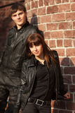 Happy young couple in leather jackets at the wall Royalty Free Stock Image