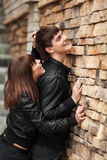 Happy young couple in leather jackets at the wall Royalty Free Stock Photos