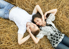 Happy young couple lie in straw, wheaten field at evening, romantic people concept, beautiful landscape, summer season Royalty Free Stock Photos