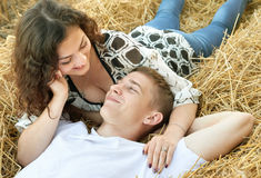 Happy young couple lie in straw, wheaten field at evening, romantic people concept, beautiful landscape, summer season Royalty Free Stock Images