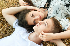 Happy young couple lie in straw, wheaten field at evening, romantic people concept, beautiful landscape, summer season Stock Photography