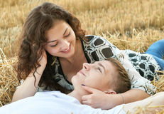 Happy young couple lie in straw, wheaten field at evening, romantic people concept, beautiful landscape, summer season Stock Image