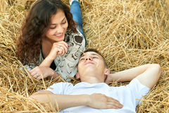 Happy young couple lie in straw, wheaten field at evening, romantic people concept, beautiful landscape, summer season Stock Images