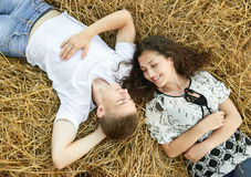 Happy young couple lie in straw, wheaten field at evening, romantic people concept, beautiful landscape, summer season Royalty Free Stock Image