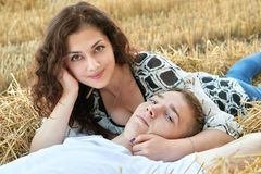 Happy young couple lie in straw, wheaten field at evening, romantic people concept, beautiful landscape, summer season Stock Photo