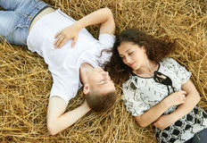Happy young couple lie in straw, wheaten field at evening, romantic people concept, beautiful landscape, summer season Stock Photos