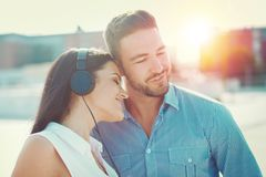 Happy young couple listening music by headphones outdoors royalty free stock photos