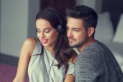 Happy young couple listening music at home. Happy young caucasian couple listening music at home Stock Photos