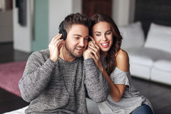 Happy young couple listening music at home on headphones Royalty Free Stock Photo