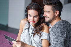 Happy young couple listening music indoor. On tablet Royalty Free Stock Photos