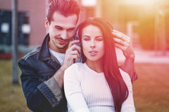Happy young couple listening music outdoor. By headphones in sunset Stock Images