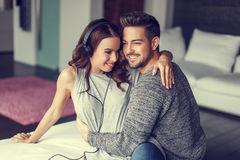 Happy young couple listening to music indoor stock photos