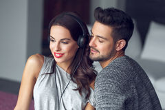 Happy young couple listening to music indoor with love Royalty Free Stock Images