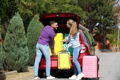 Happy young couple loading suitcases in car trunk. Outdoors royalty free stock images