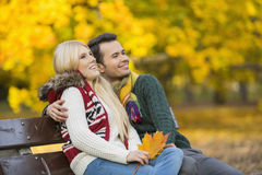 Happy young couple looking away while sitting on park bench during autumn Royalty Free Stock Photos