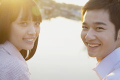 Happy Young Couple Looking at the Camera by a River Royalty Free Stock Photo