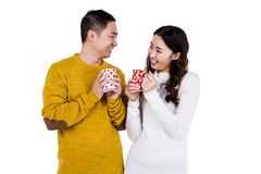 Happy young couple looking at each other while holding cups. Against white background Stock Image