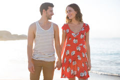 Happy young couple looking at each other while holding hands at beach Stock Photography
