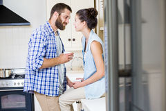 Happy young couple looking each other in kitchen. At home Royalty Free Stock Images