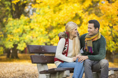 Happy young couple looking at each other while sitting on park bench during autumn stock photos