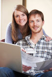 Happy Young Couple Looking At Finances On Laptop. Happy Young Couple Look At Finances On Laptop Royalty Free Stock Photos