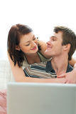 Happy young couple looking in laptop Stock Photos