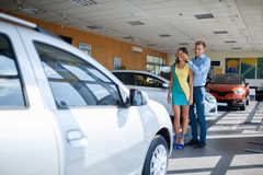 Guy prepared a surprise for his girlfriend. Buying a new car. Happy young couple looking at new car in showroom. The concept of buying a new car Stock Photography