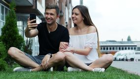 Happy young couple looking at smartphone, have video call, calling friends or relatives, social media stock video footage