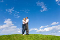 Happy young couple looking at something. Above a green meadow. Against the backdrop of blue sky Royalty Free Stock Images