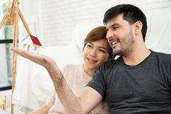 Young couple with house model. Happy young couple looking to house model together. Smiling stock photo