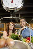Happy young couple looking at weight scale in supermarket Stock Photo