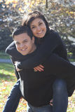 Happy young couple in love. Half body portrait of happy young couple in love with man giving woman piggy back ride, park in background stock photos