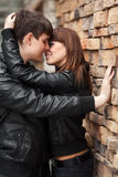 Happy young fashion couple in love at the brick wall Royalty Free Stock Photos