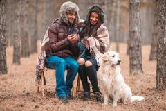 A happy couple with a dog is sitting in a forest, drinking tea and laughing. Outdoors. royalty free stock photos