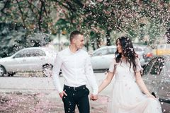 Happy young couple in love enjoys spring day, loving man holding on hands his woman carefree walking at park stock image