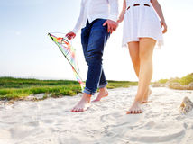 Happy young couple in love with flying a kite. On the beach stock images