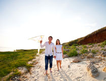 Happy young couple in love with flying a kite. On the beach royalty free stock image