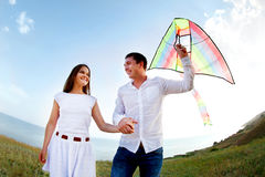 Happy young couple in love with flying a kite. On the beach stock photography