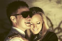 Happy young couple in love at the grungy wall stock image