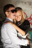 Happy young couple in love at the grungy wall Stock Images