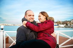 Lifestyle image of cheerful young couple in love having fun on lonely beach together . Spring or fall time. Sincerest Royalty Free Stock Image