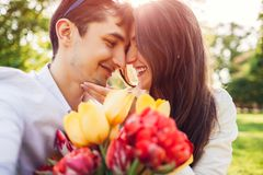 Happy young couple in love hugging with spring flower bouquet outdoors. Man gifted his girlfriend with tulips royalty free stock images