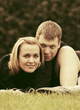 Happy young couple in love lying on the grass Royalty Free Stock Photography