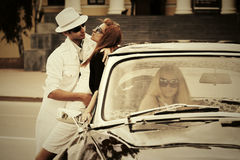 Happy young couple in love next to retro car Stock Photography