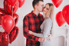 Happy young couple in love posing with red heart balloons Stock Photography