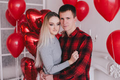 Happy young couple in love posing with red heart balloons Royalty Free Stock Image