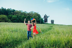Happy young couple in love runing a kite on the field. Two, man and woman smiling and resting in the country side. Happycouple in love runing a kite on the field Stock Images