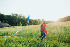 Happy young couple in love runing a kite on the field. Two, man and woman smiling and resting in the country side. Happy couple in love runing a kite on the Stock Images