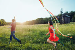 Happy young couple in love runing a kite on the field. Two, man and woman smiling and resting in the country side. Happy couple in love runing a kite on the Stock Image