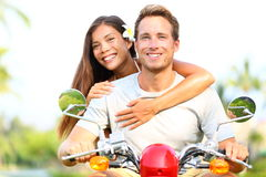 Happy young couple in love on scooter. Driving together. Multiracial couple having fun in the free outdoor. Smiling Caucasian men and Asian woman Royalty Free Stock Photography